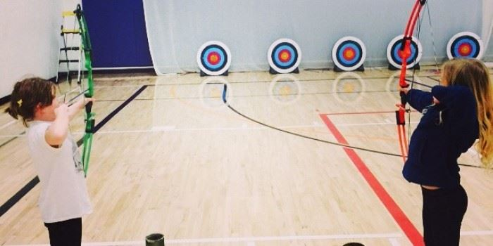 Kids practicing archery in a gymnasium.